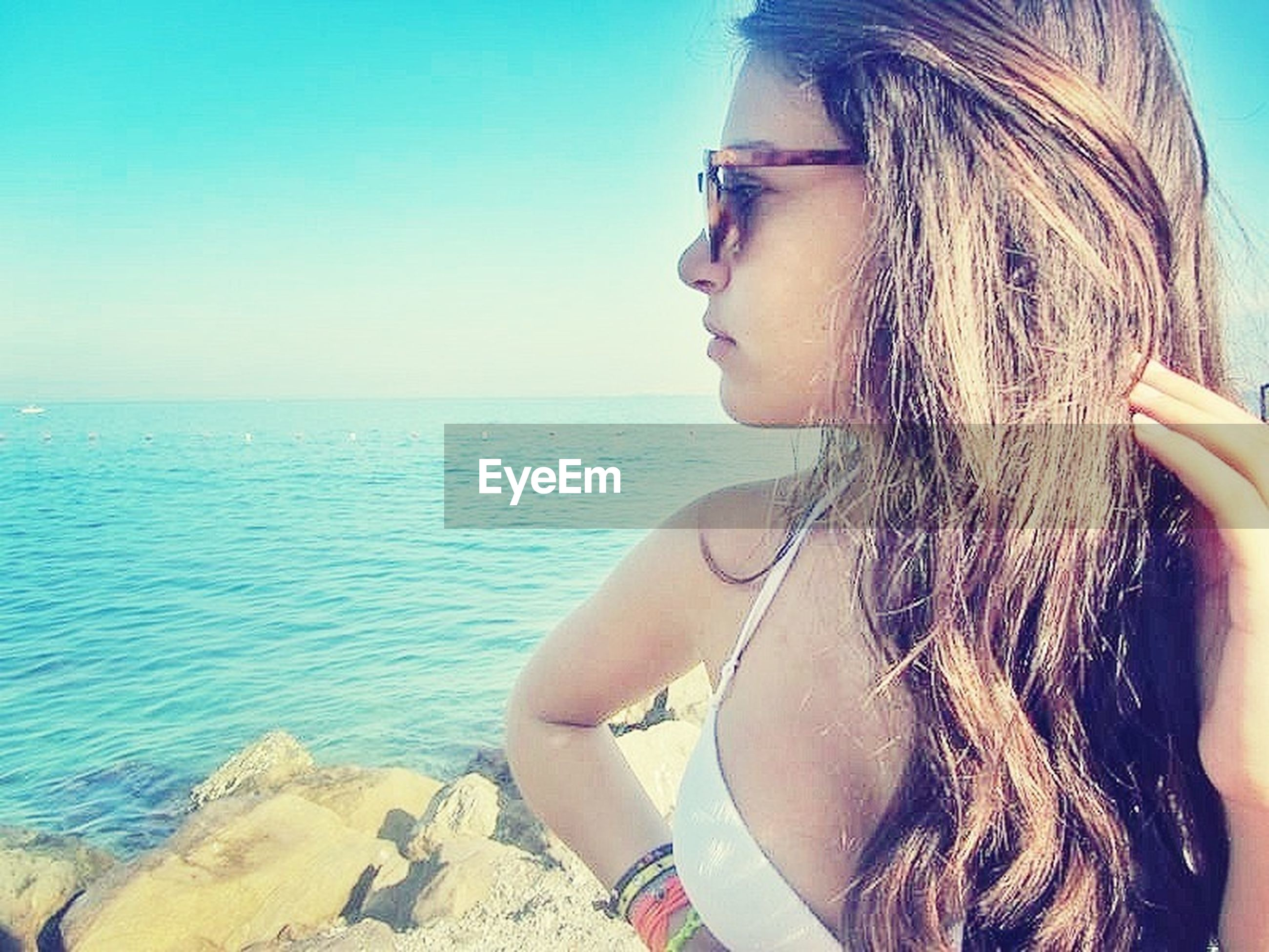 sea, water, young adult, horizon over water, sunglasses, leisure activity, lifestyles, young women, clear sky, long hair, sunlight, beach, vacations, person, headshot, transportation, sky, copy space