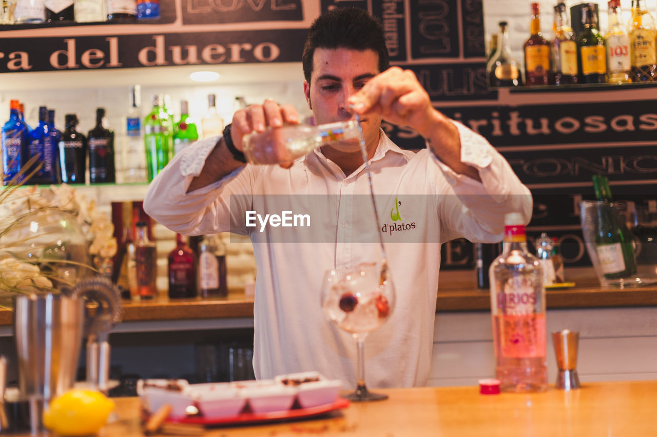 Bartender Preparing Drink At Counter