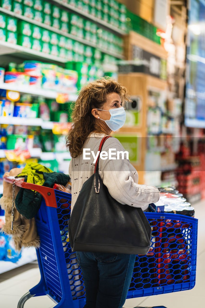 Side view of woman wearing mask standing at shopping mall