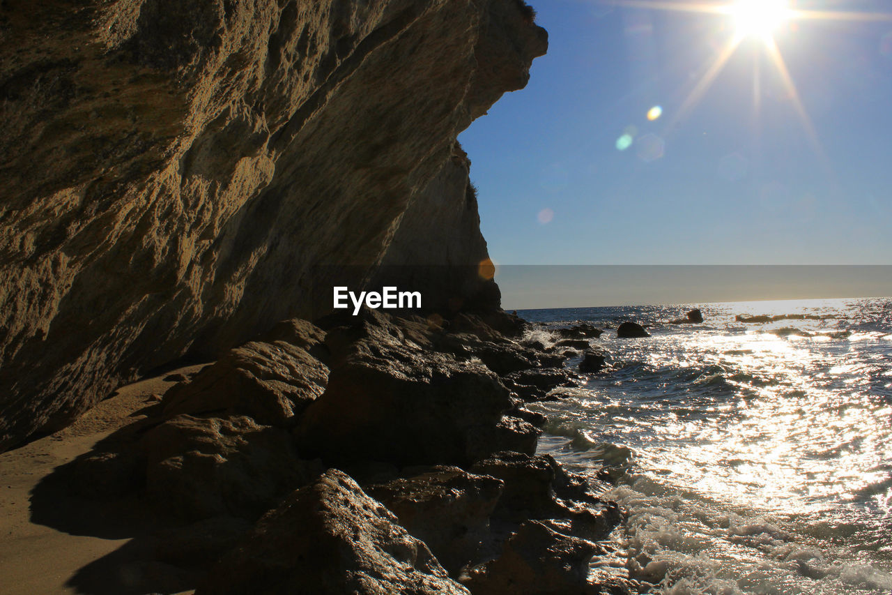 sea, rock, sky, water, rock - object, sunlight, beauty in nature, solid, sun, scenics - nature, nature, rock formation, lens flare, sunbeam, beach, land, tranquility, tranquil scene, day, outdoors, no people, horizon over water, bright, eroded