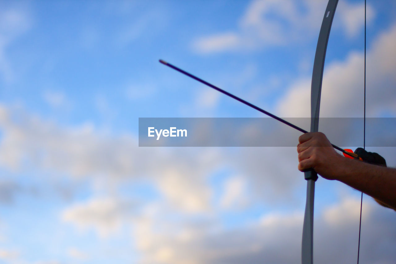 Cropped Image Of Man Holding Archery Bow Against Sky