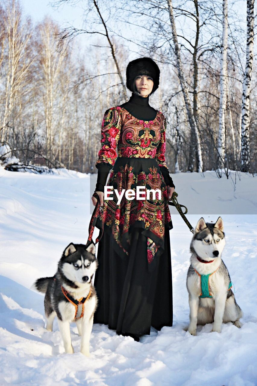 Woman wearing traditional costume with siberian huskies on snowy field