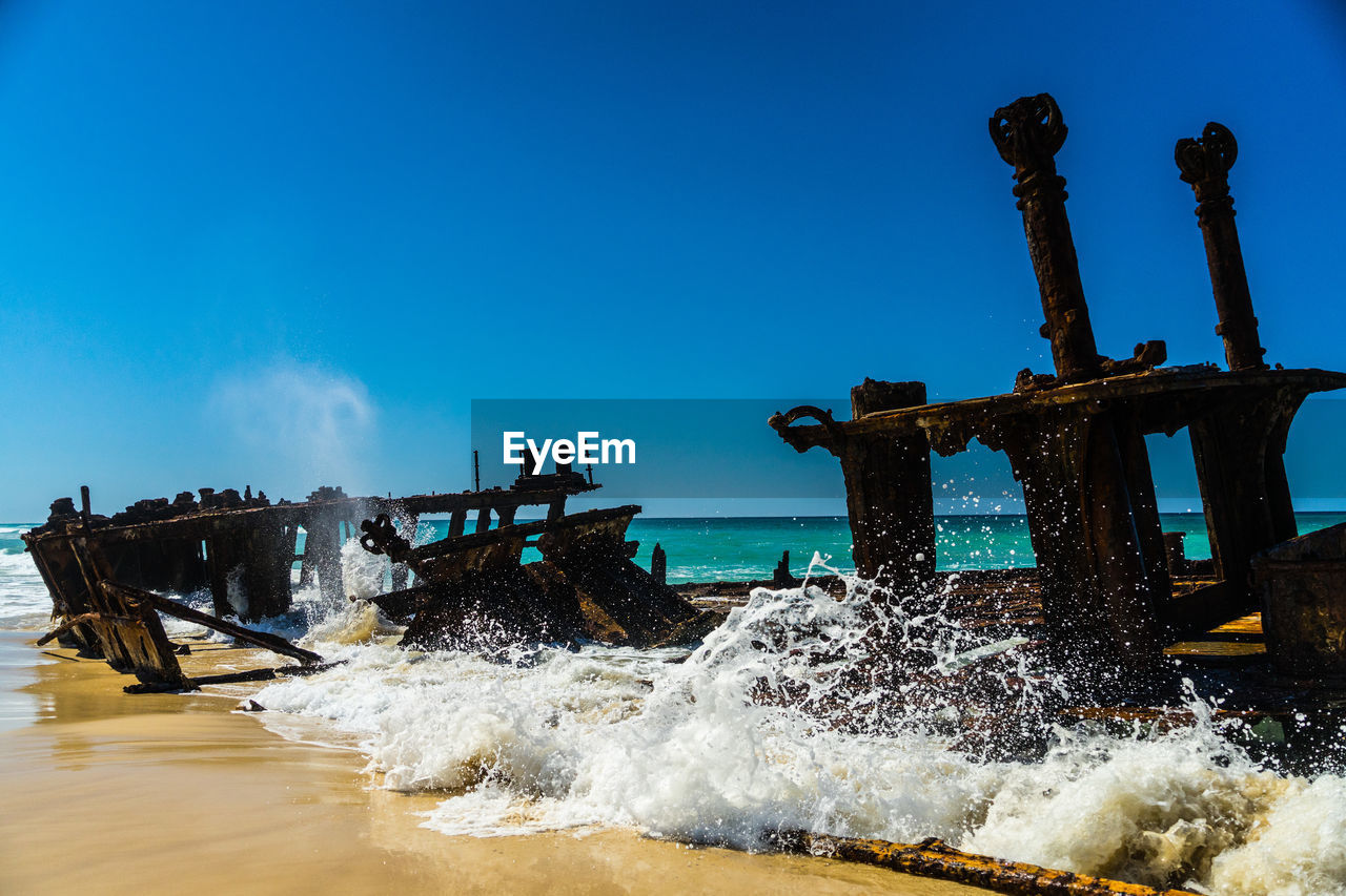 water, sea, sky, motion, nature, blue, splashing, day, crash, beauty in nature, clear sky, outdoors, no people, copy space, wave, architecture, breaking, damaged, aquatic sport, power in nature, deterioration, hitting