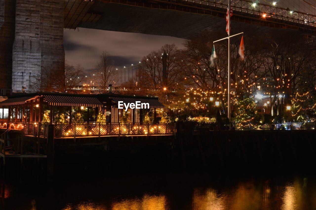 VIEW OF ILLUMINATED BRIDGE OVER RIVER