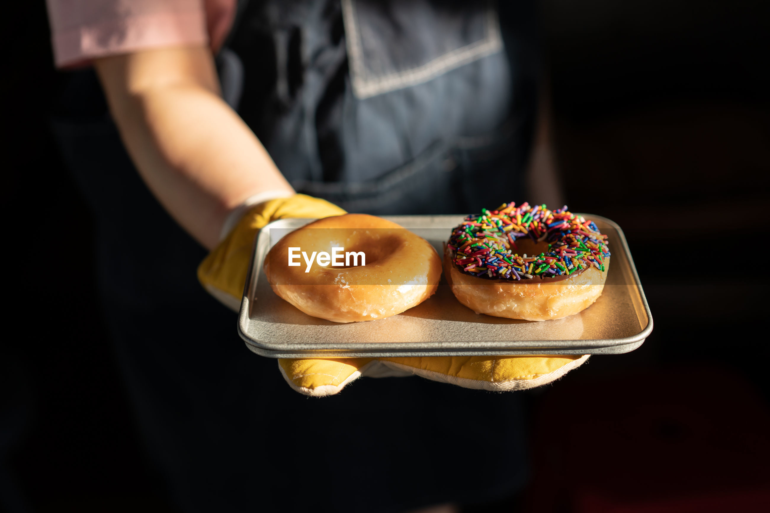 Midsection of person holding donut against black background