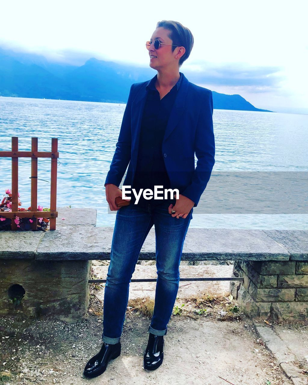 one person, water, real people, young adult, casual clothing, front view, sea, standing, lifestyles, fashion, leisure activity, glasses, full length, sunglasses, sky, day, nature, young men, outdoors, jeans