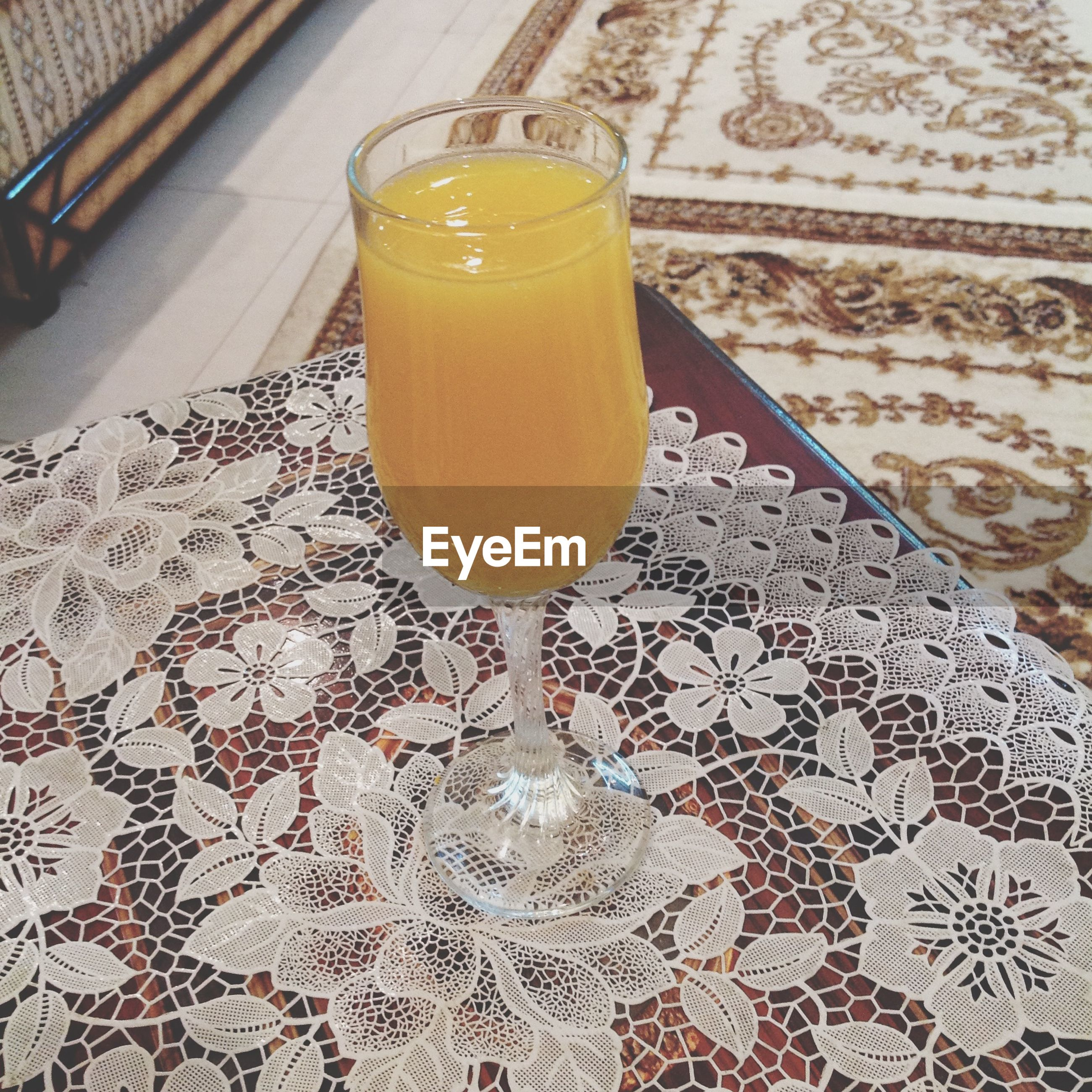 indoors, drink, refreshment, food and drink, table, drinking glass, still life, freshness, glass - material, yellow, close-up, alcohol, high angle view, glass, transparent, no people, restaurant, juice, home interior, drinking straw