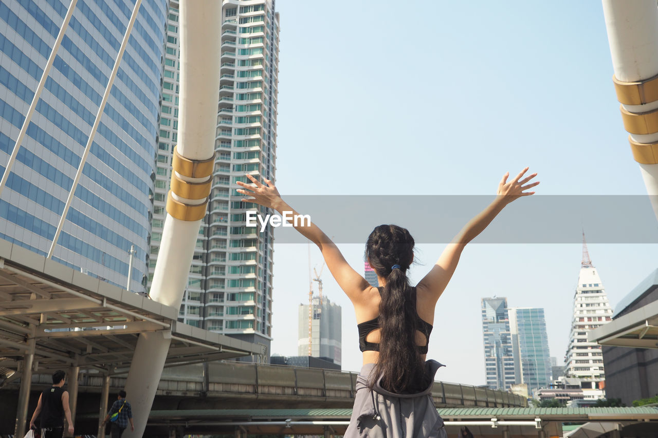 Rear View Of Woman With Arms Outstretched Standing Against Clear Sky In City