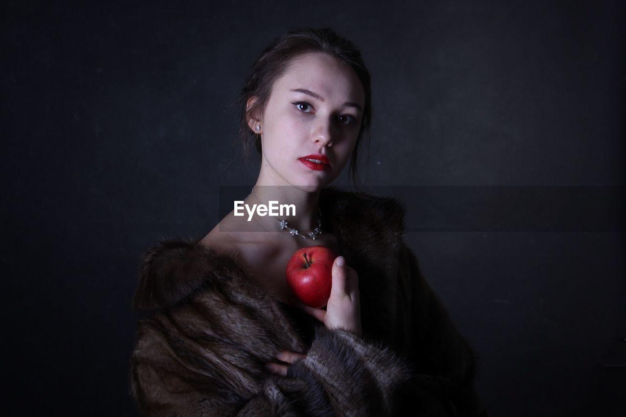 Portrait of woman holding apple against black background