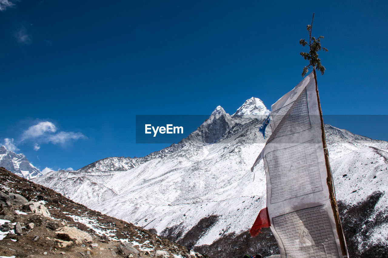 sky, snow, winter, belief, cold temperature, mountain, religion, spirituality, nature, low angle view, blue, day, place of worship, beauty in nature, scenics - nature, architecture, snowcapped mountain, built structure, no people, mountain range, outdoors, mountain peak