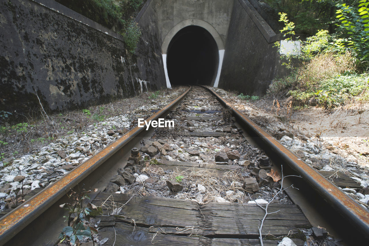 rail transportation, track, railroad track, transportation, the way forward, direction, architecture, no people, solid, tunnel, day, diminishing perspective, arch, nature, built structure, connection, rock, stone - object, outdoors, rock - object, gravel, surface level, long