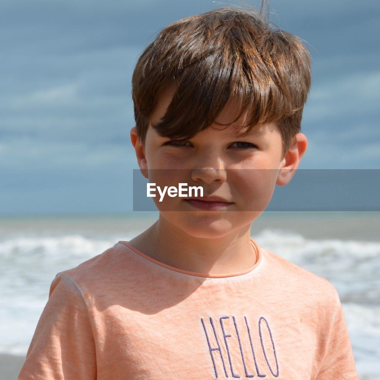 Portrait Of Boy At Beach Against Sky
