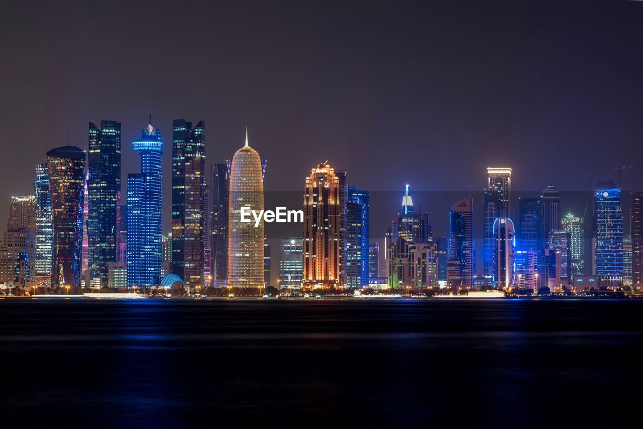 architecture, building exterior, illuminated, night, skyscraper, city, built structure, cityscape, tower, tall - high, travel destinations, urban skyline, modern, waterfront, downtown district, tourism, no people, outdoors, water, sky, sea