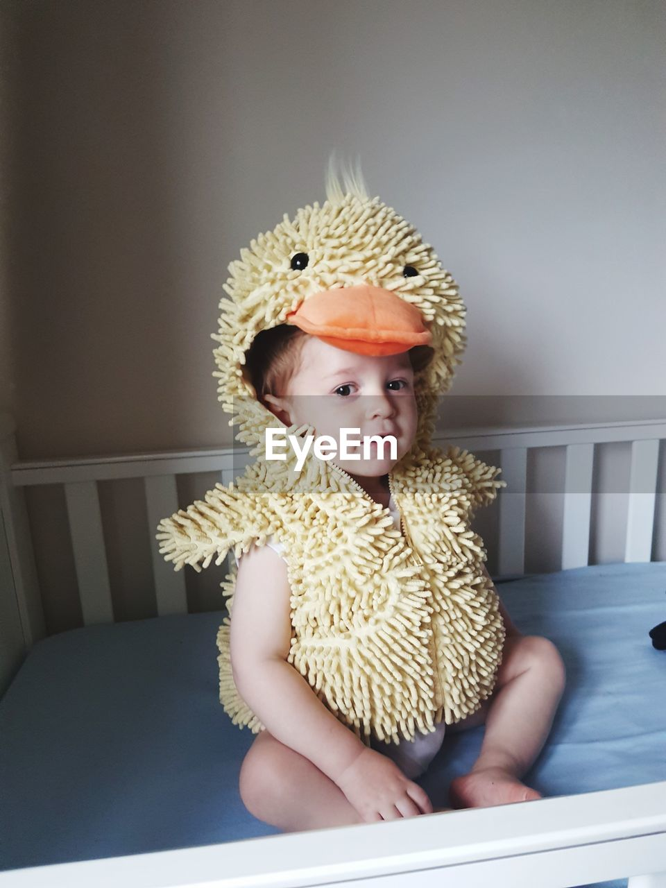 Portrait Of Toddler Wearing Costume Sitting On Bed At Home