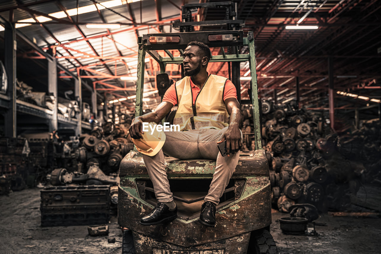 Full length of worker sitting on forklift at factory