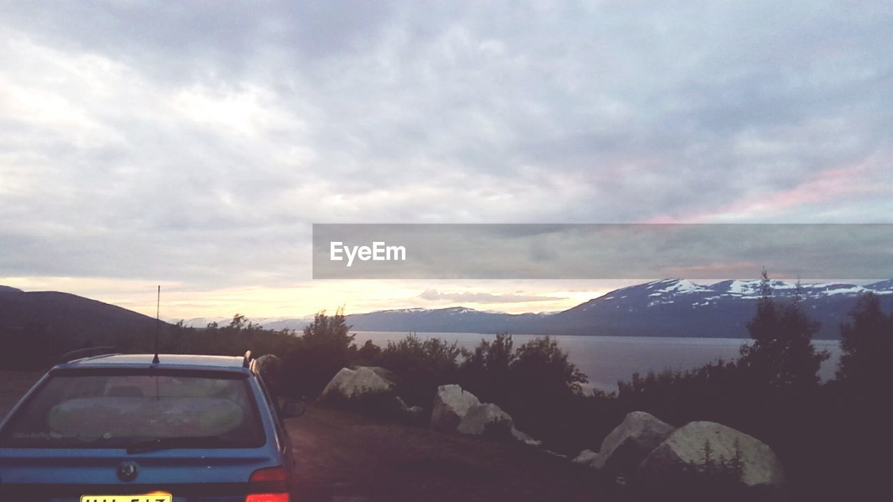 mountain, sky, scenics, nature, mountain range, beauty in nature, cloud - sky, water, transportation, car, outdoors, sunset, no people, landscape, road, day