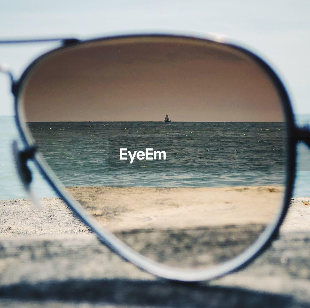 Close-up of sea seen through sunglasses