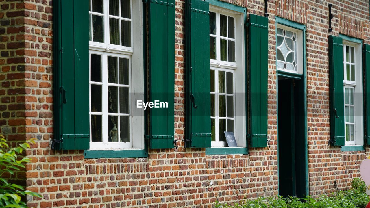 window, brick wall, building exterior, architecture, built structure, brick, outdoors, day, door, no people, city