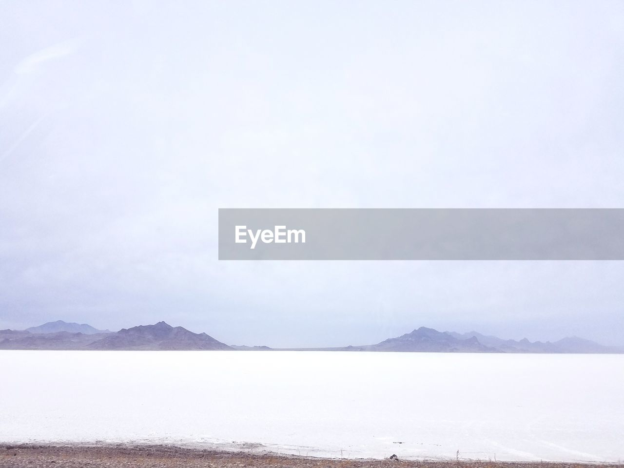 mountain, scenics, tranquility, tranquil scene, beauty in nature, nature, outdoors, landscape, water, day, no people, lake, mountain range, cold temperature, fog, snow, sky, salt flat