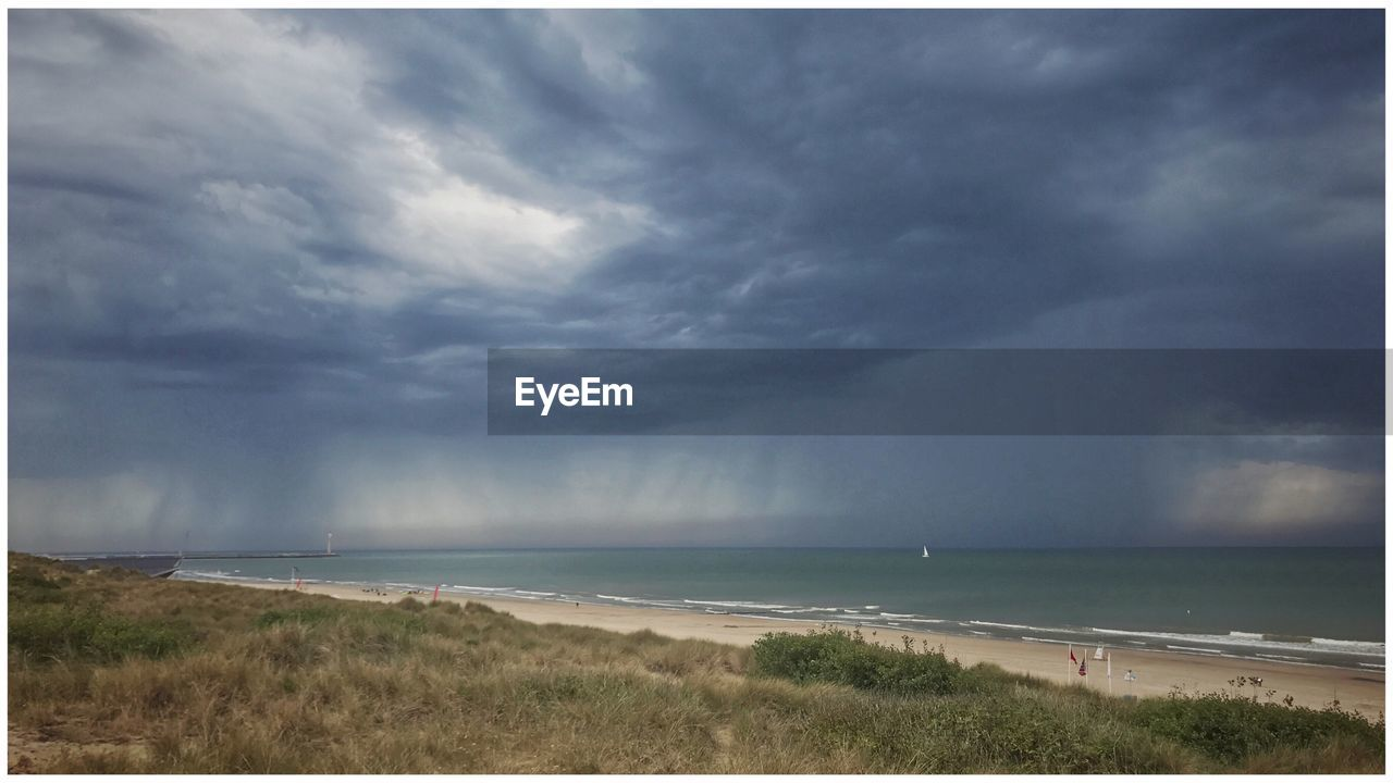 sea, horizon over water, cloud - sky, nature, water, scenics, sky, beauty in nature, storm cloud, storm, weather, environment, tranquil scene, thunderstorm, beach, outdoors, tranquility, no people, landscape, day, grass, scenery, power in nature