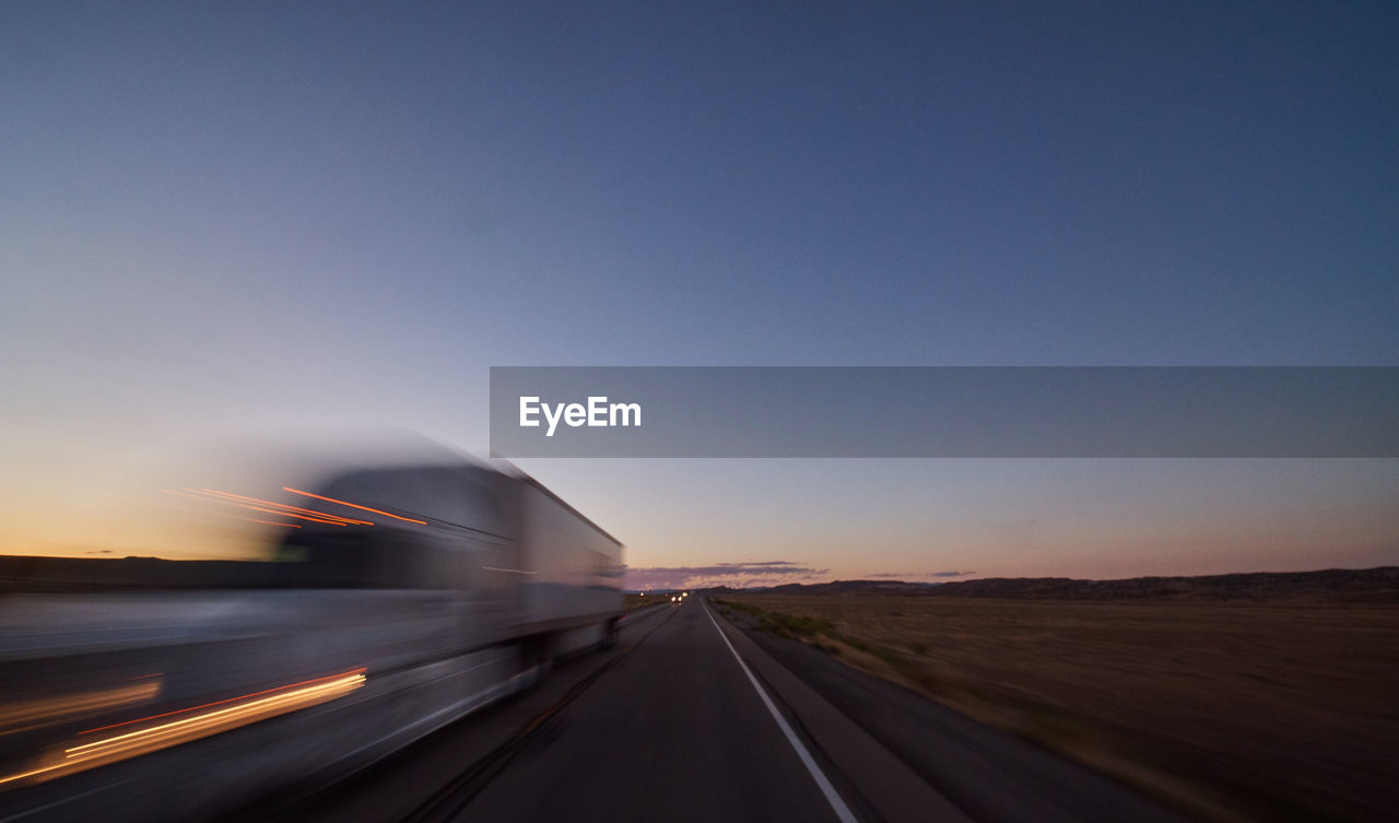 transportation, blurred motion, motion, sky, road, speed, copy space, no people, mode of transportation, land vehicle, sunset, the way forward, on the move, nature, motor vehicle, clear sky, symbol, direction, long exposure, travel, outdoors, diminishing perspective