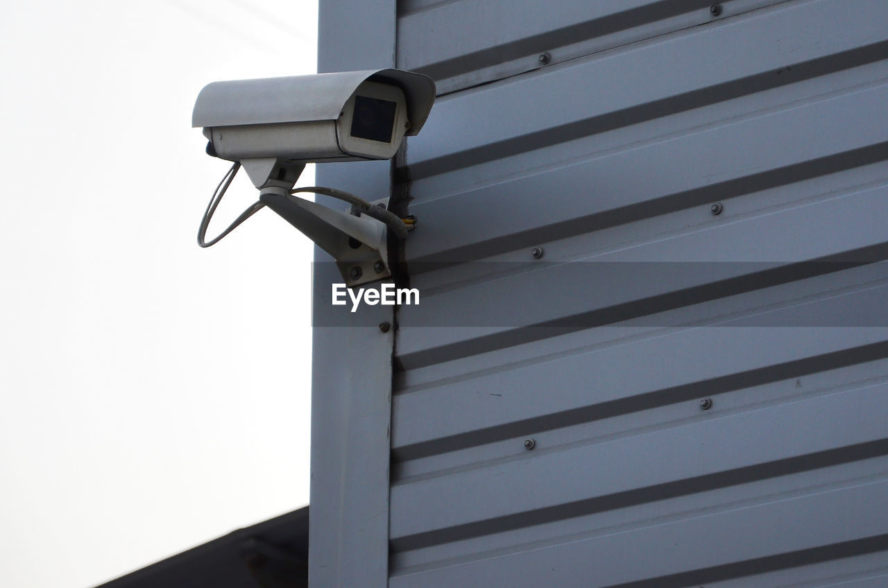 security camera, surveillance, security system, security, low angle view, no people, technology, protection, safety, metal, outdoors, day, architecture, built structure, control, close-up, wall - building feature, sky, sunlight, nature, home video camera