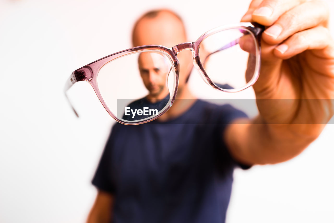 CLOSE-UP OF YOUNG MAN HOLDING EYEGLASSES