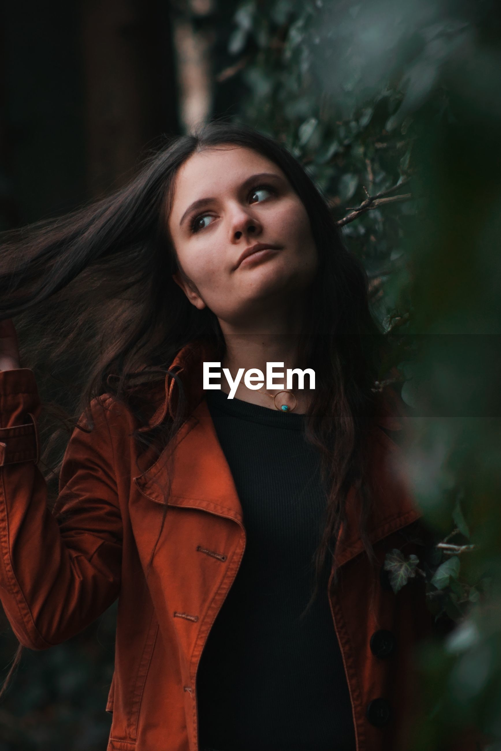 Beautiful young woman looking away while standing against plants