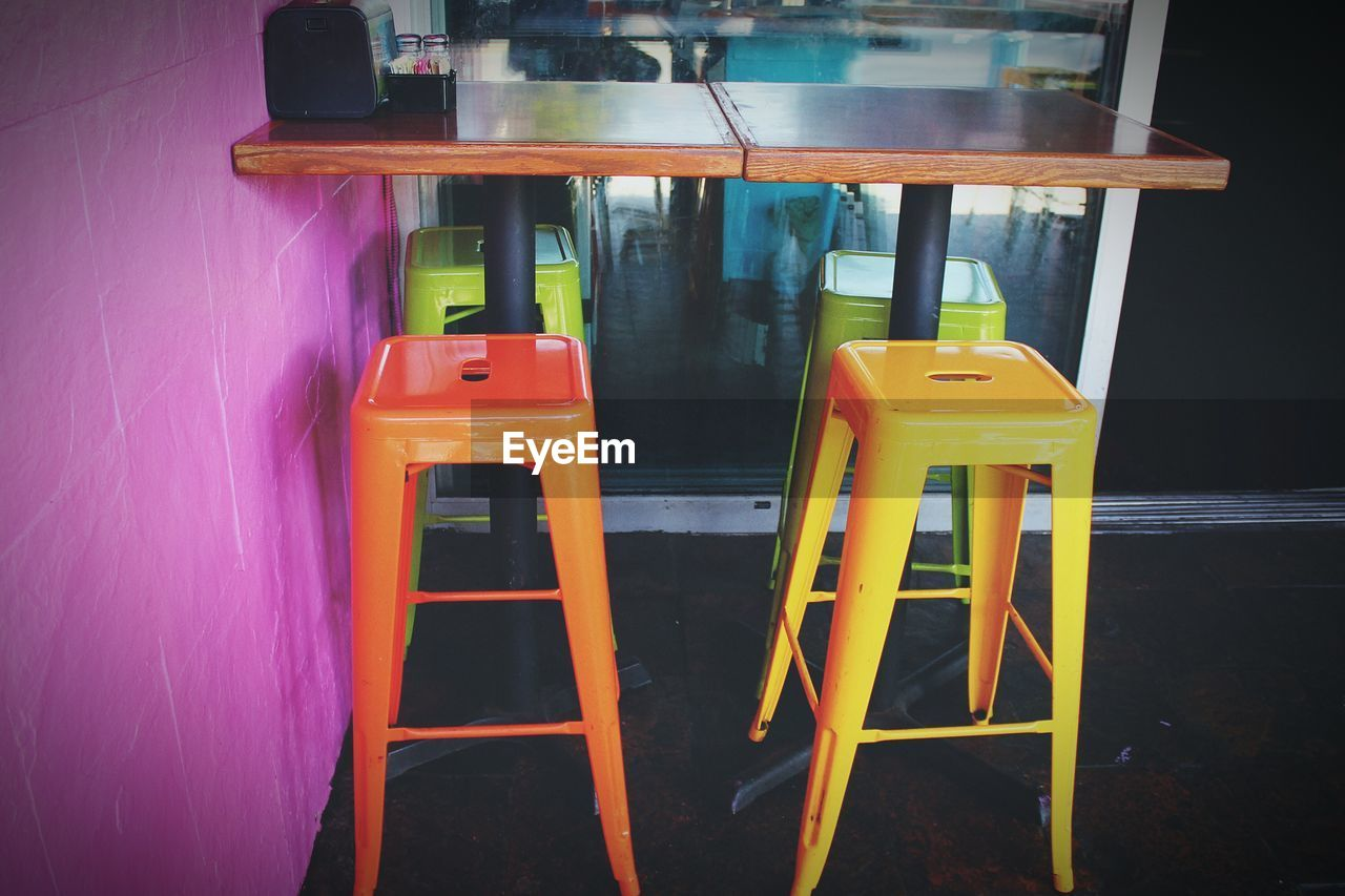 absence, no people, empty, yellow, table, seat, indoors, chair, multi colored, architecture, red, day, wood - material, cafe, reflection, restaurant, close-up, water