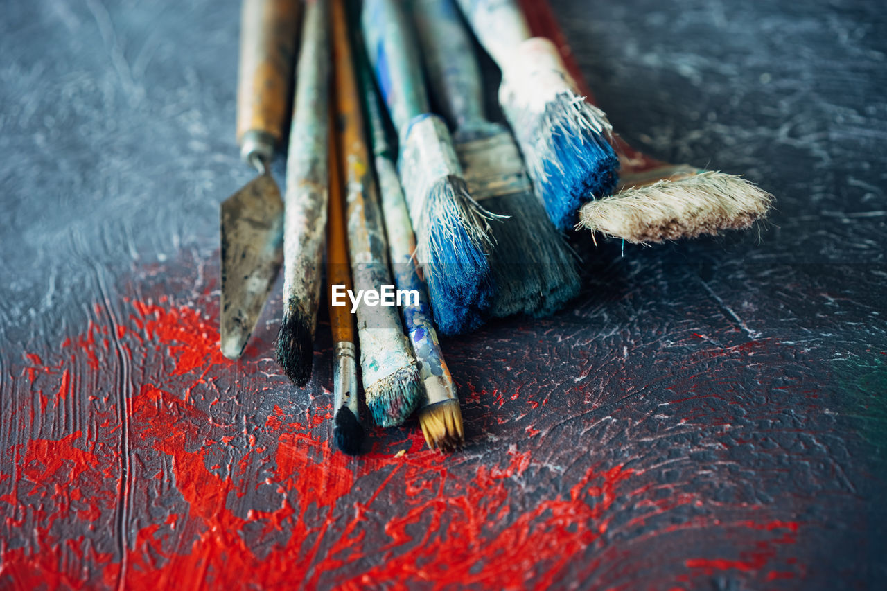 Close-Up Of Paintbrushes On Messy Table