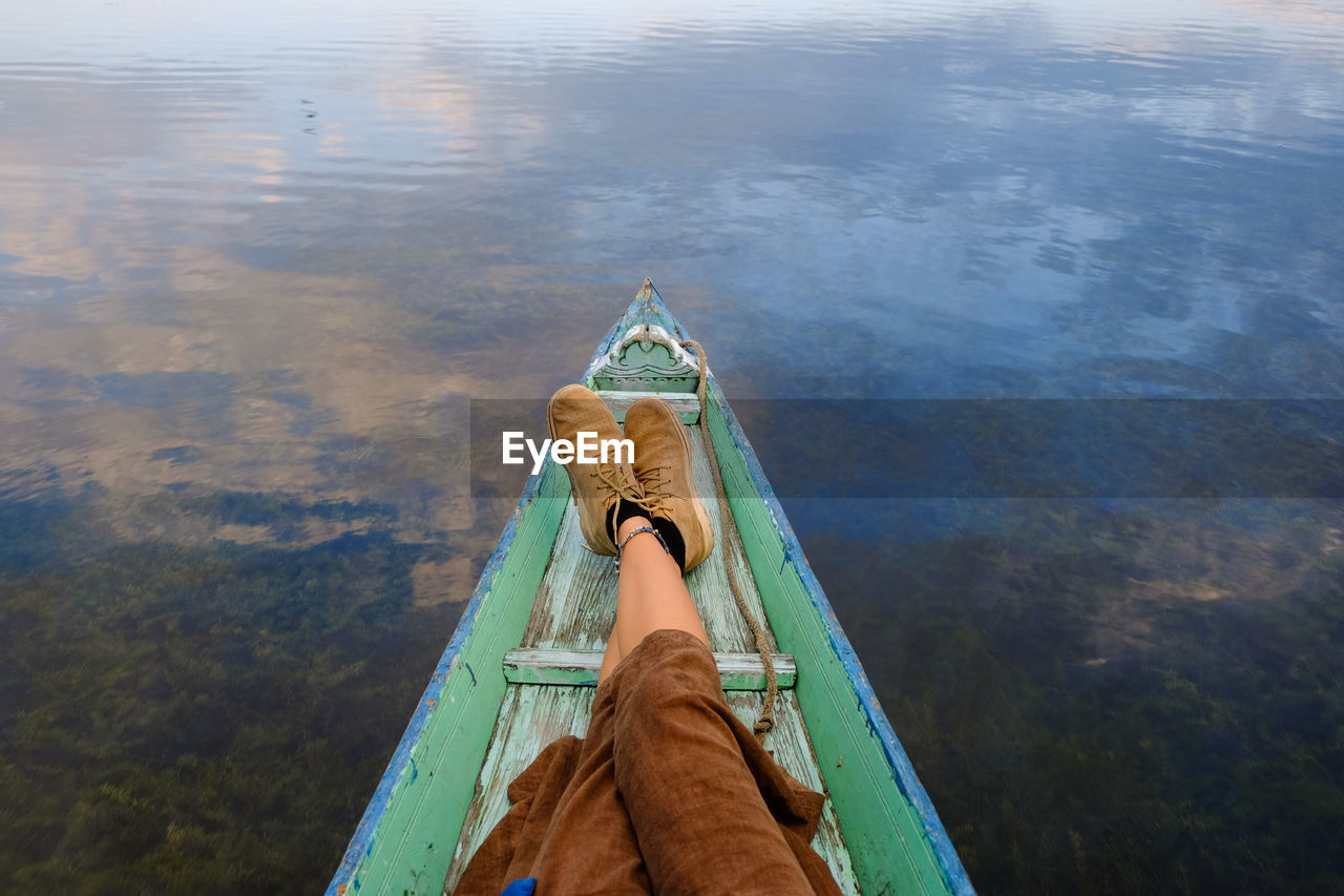 Low Section Of Person In Boat On Lake
