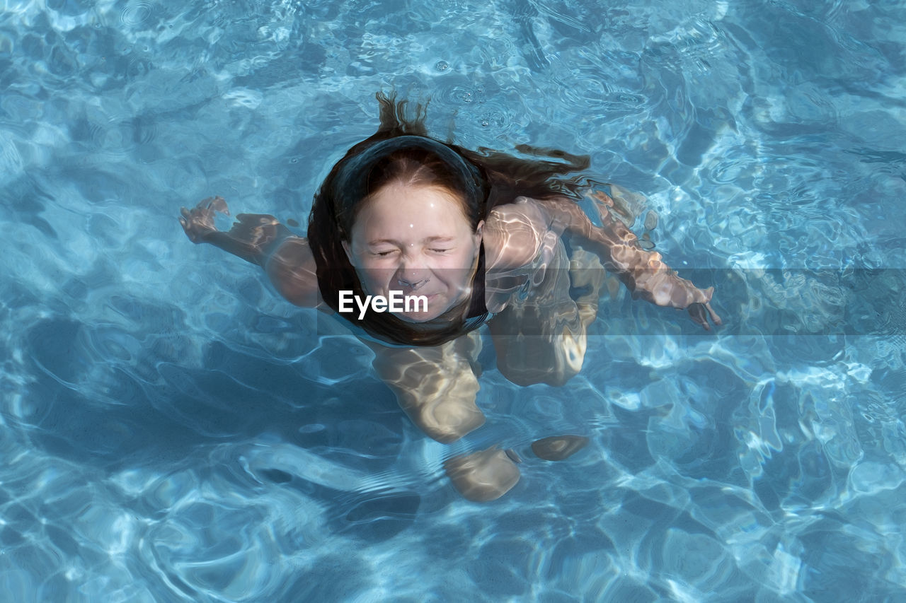 High Angle View Of Girl Swimming In Pool During Sunny Day