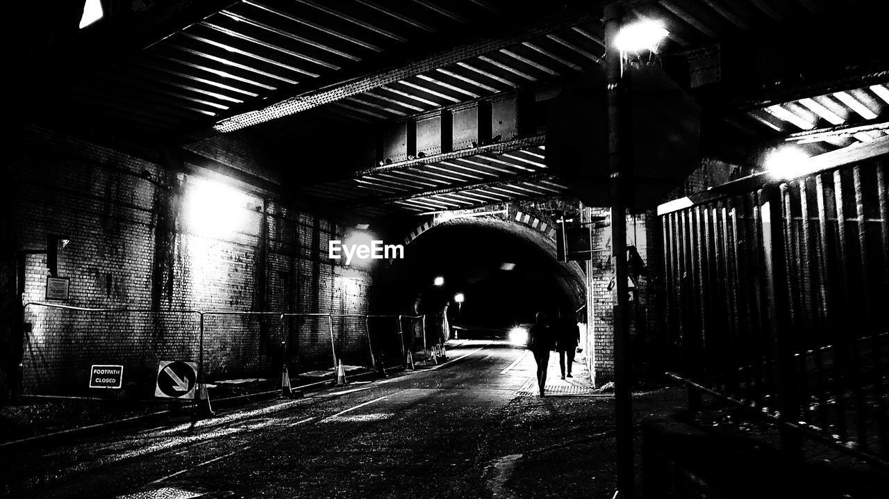 architecture, direction, built structure, the way forward, illuminated, indoors, one person, real people, tunnel, lighting equipment, transportation, full length, lifestyles, walking, rear view, arch, men, building, subway, ceiling, light, light at the end of the tunnel