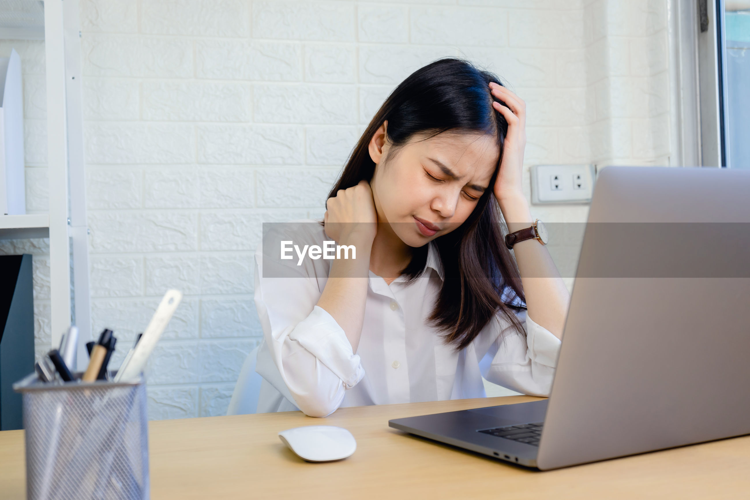 Businesswoman suffering from headache while sitting in office