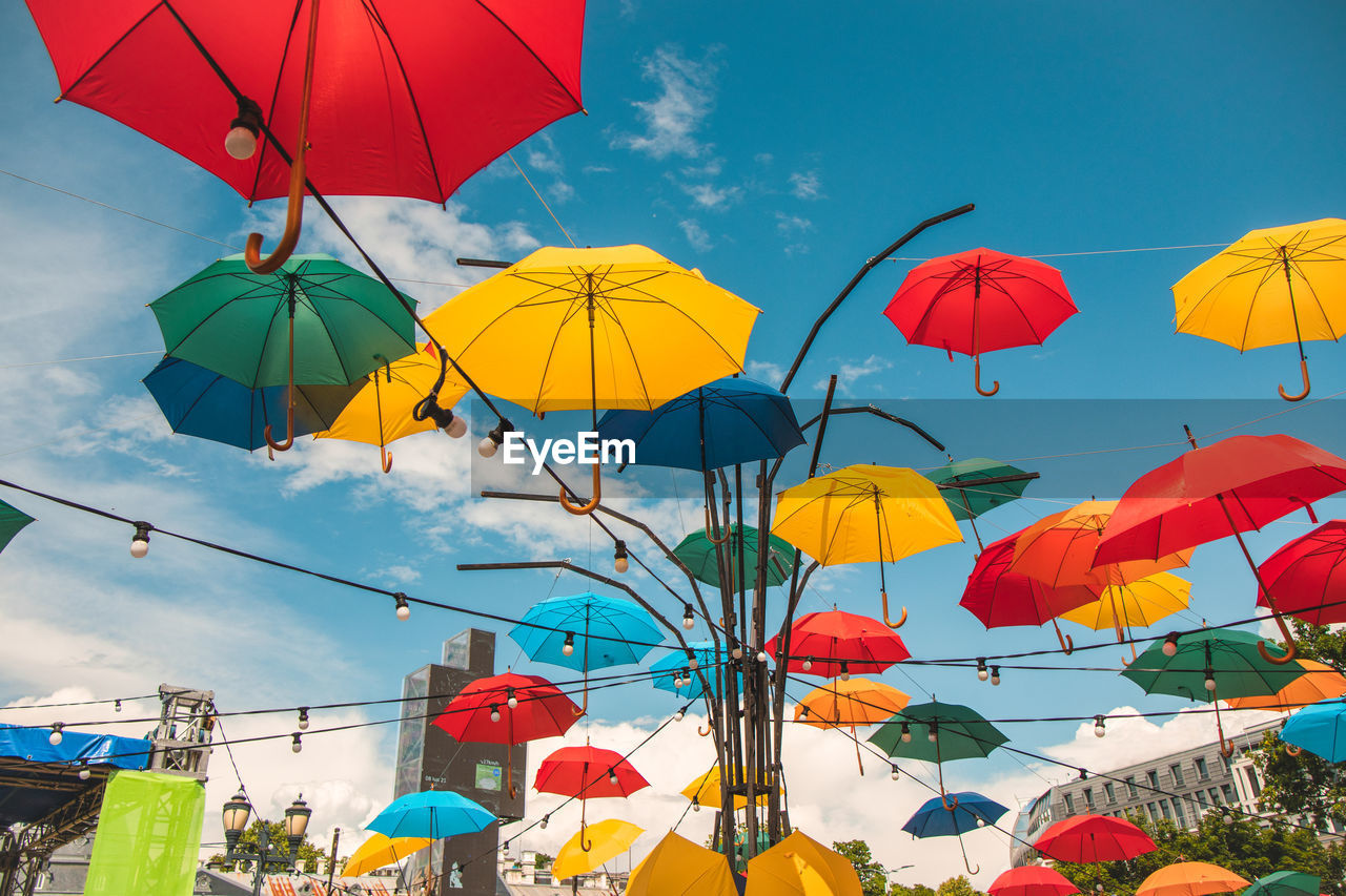 LOW ANGLE VIEW OF UMBRELLAS AGAINST SKY