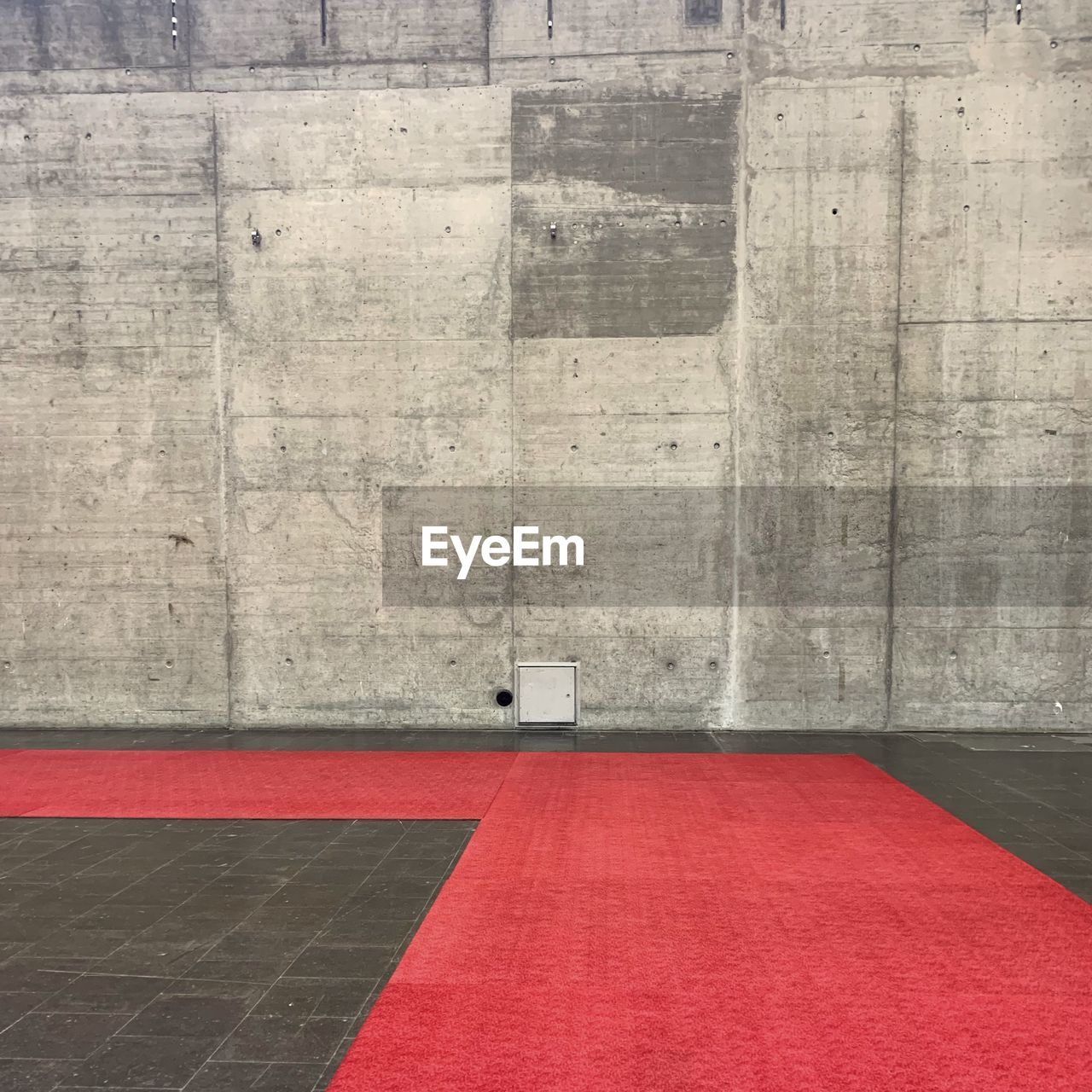 red, wall - building feature, architecture, indoors, no people, absence, built structure, carpet - decor, day, copy space, domestic room, simplicity, gray, flooring, wealth, luxury, entrance, red carpet event, security, concrete