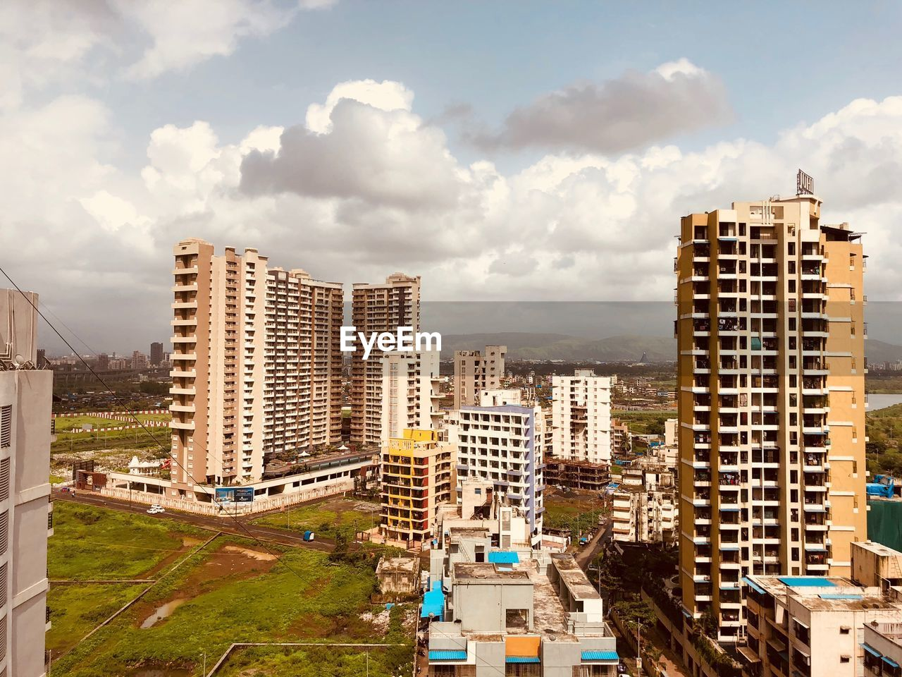building exterior, built structure, cloud - sky, architecture, sky, building, city, residential district, cityscape, nature, no people, day, office building exterior, skyscraper, tall - high, high angle view, outdoors, landscape, tower, sunlight, modern, apartment, settlement