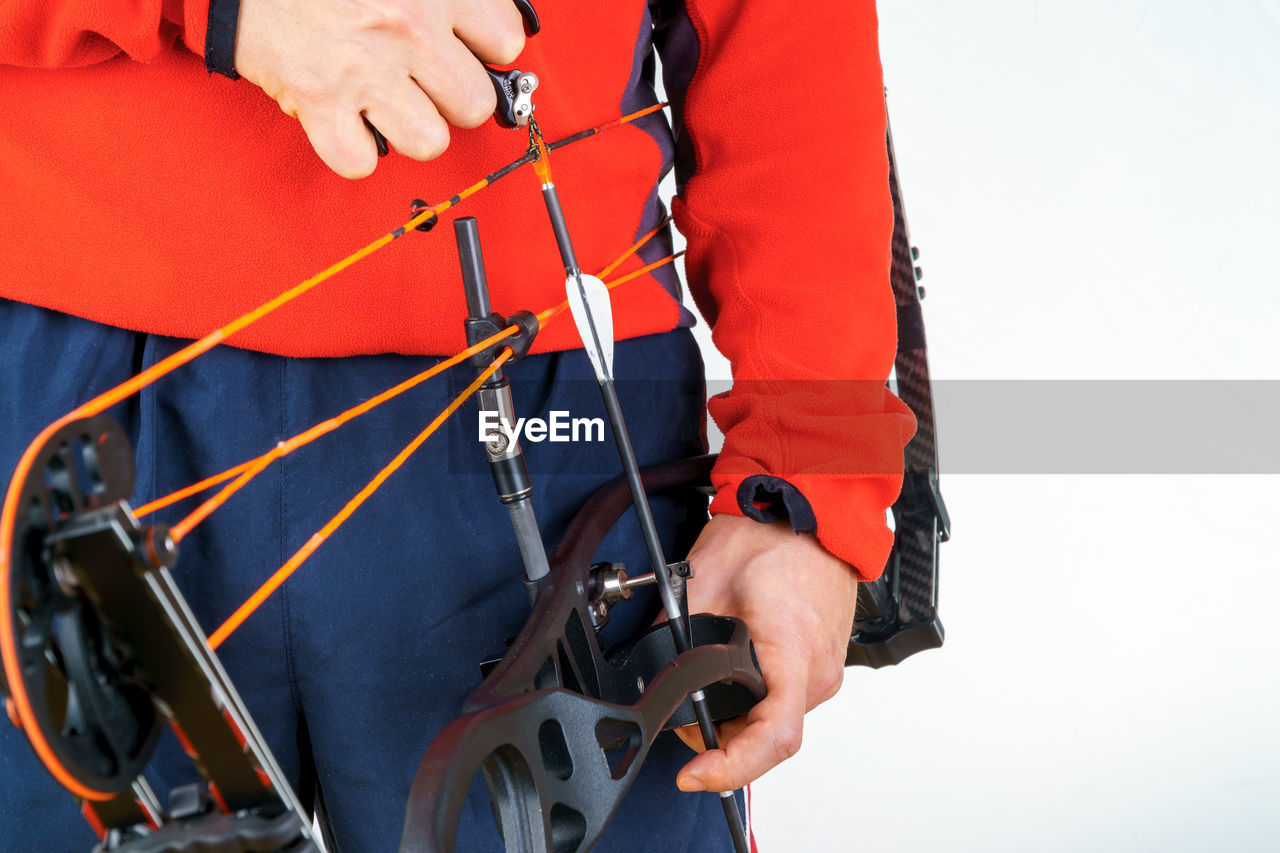 Midsection Of Archer Holding Cross Bow Against White Background