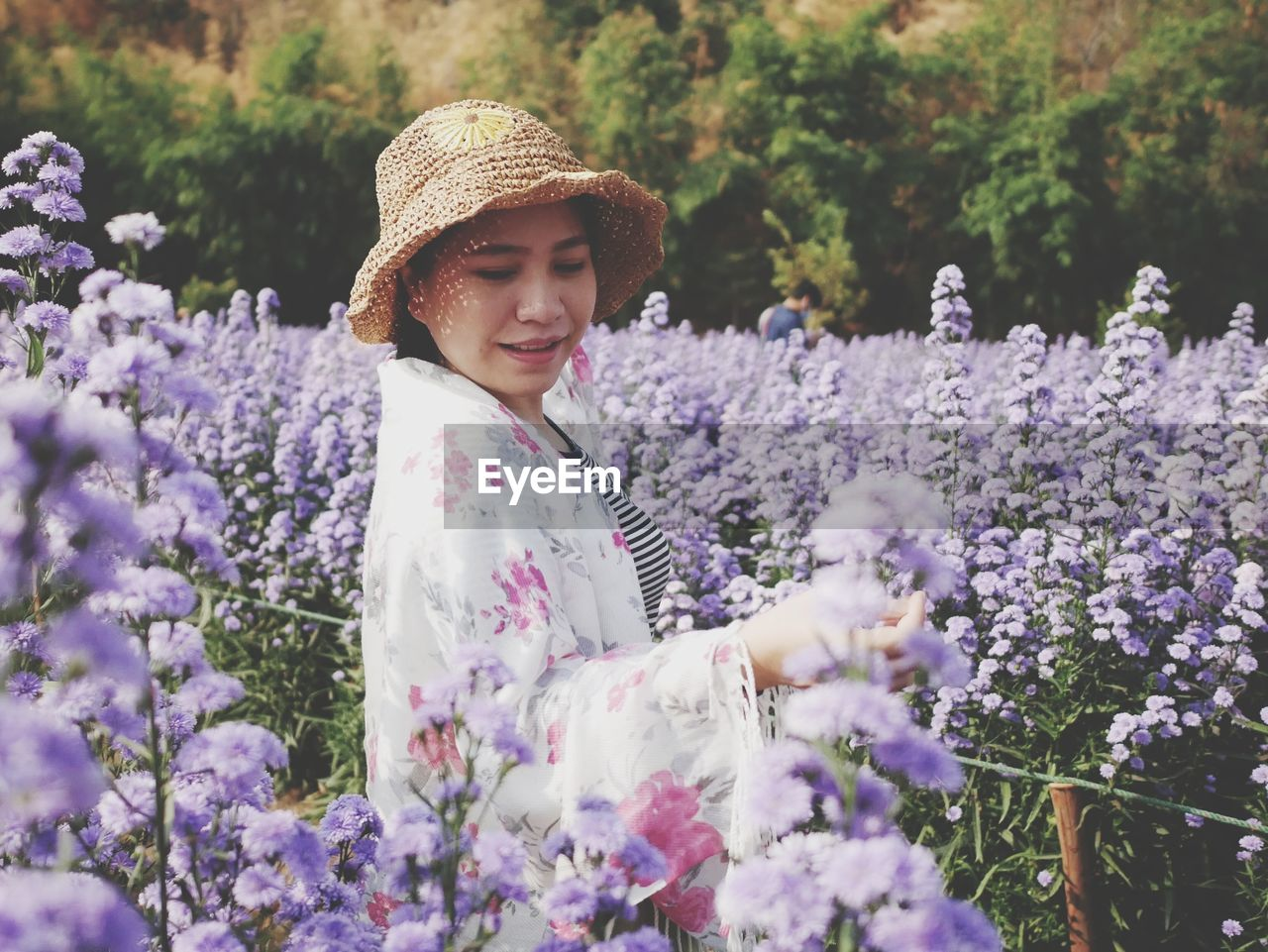 Young woman wearing hat standing amidst flowering plants