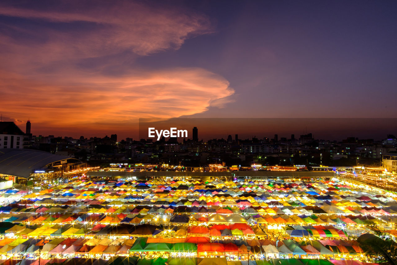 High angle view of illuminated colorful tents in market during dusk