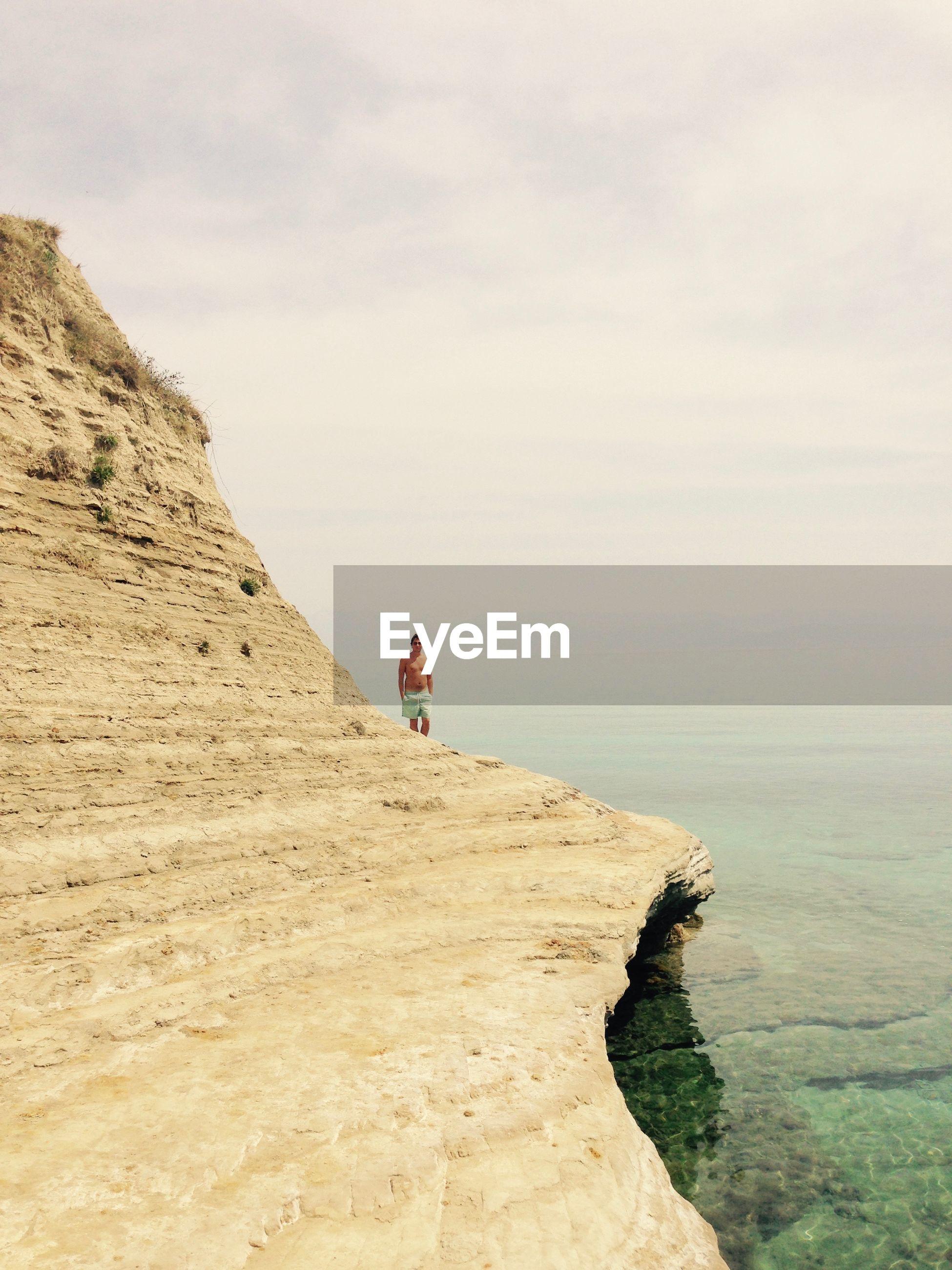 Man on cliff on beach against sky