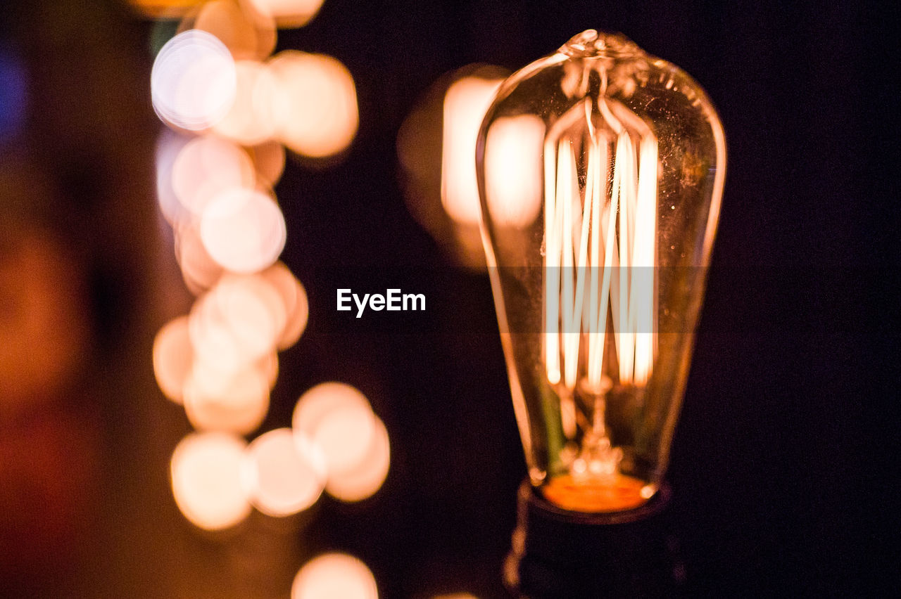 illuminated, lighting equipment, light bulb, electricity, close-up, bulb, celebration, glowing, no people, focus on foreground, black background, single object, filament, night, hanging, indoors