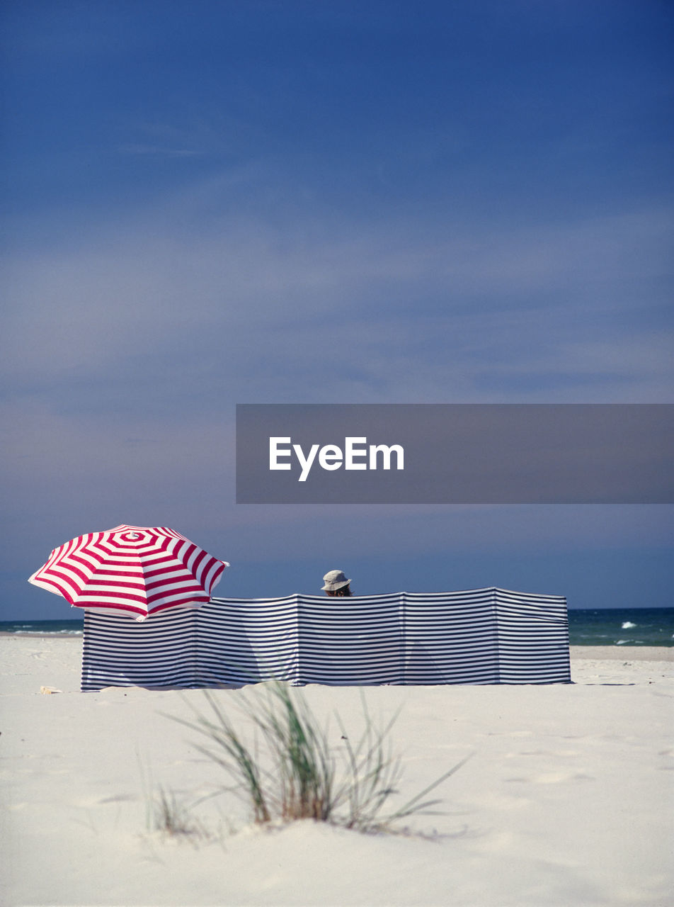 Woman Behind Striped Canvas With Red Umbrella At Beach Against Sky