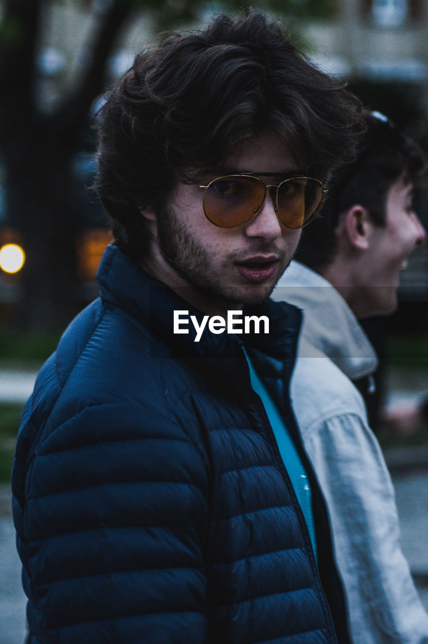 Side view portrait of young man wearing eyeglasses while walking in city