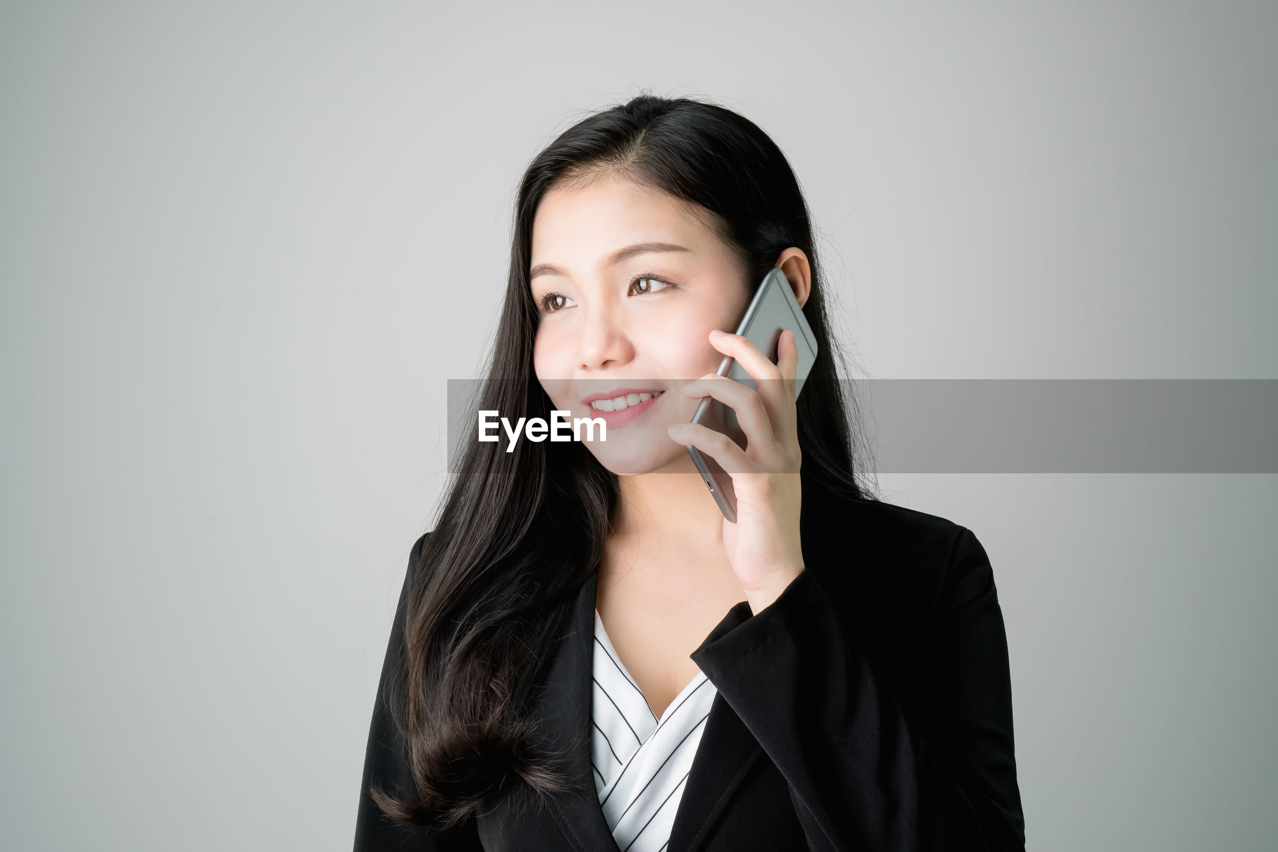 Young woman talking on mobile phone against gray background