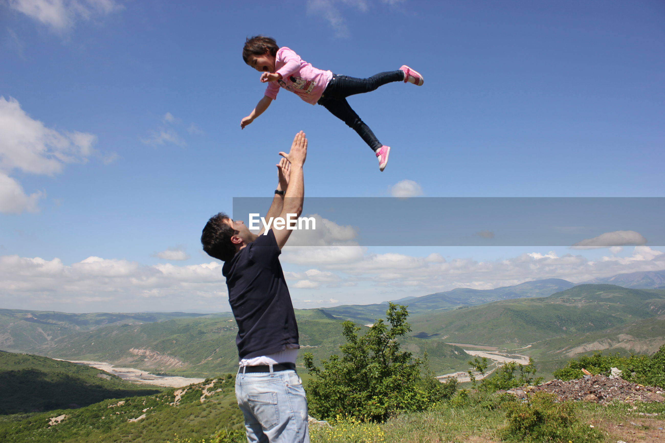FULL LENGTH OF MAN WITH ARMS RAISED AGAINST MOUNTAIN