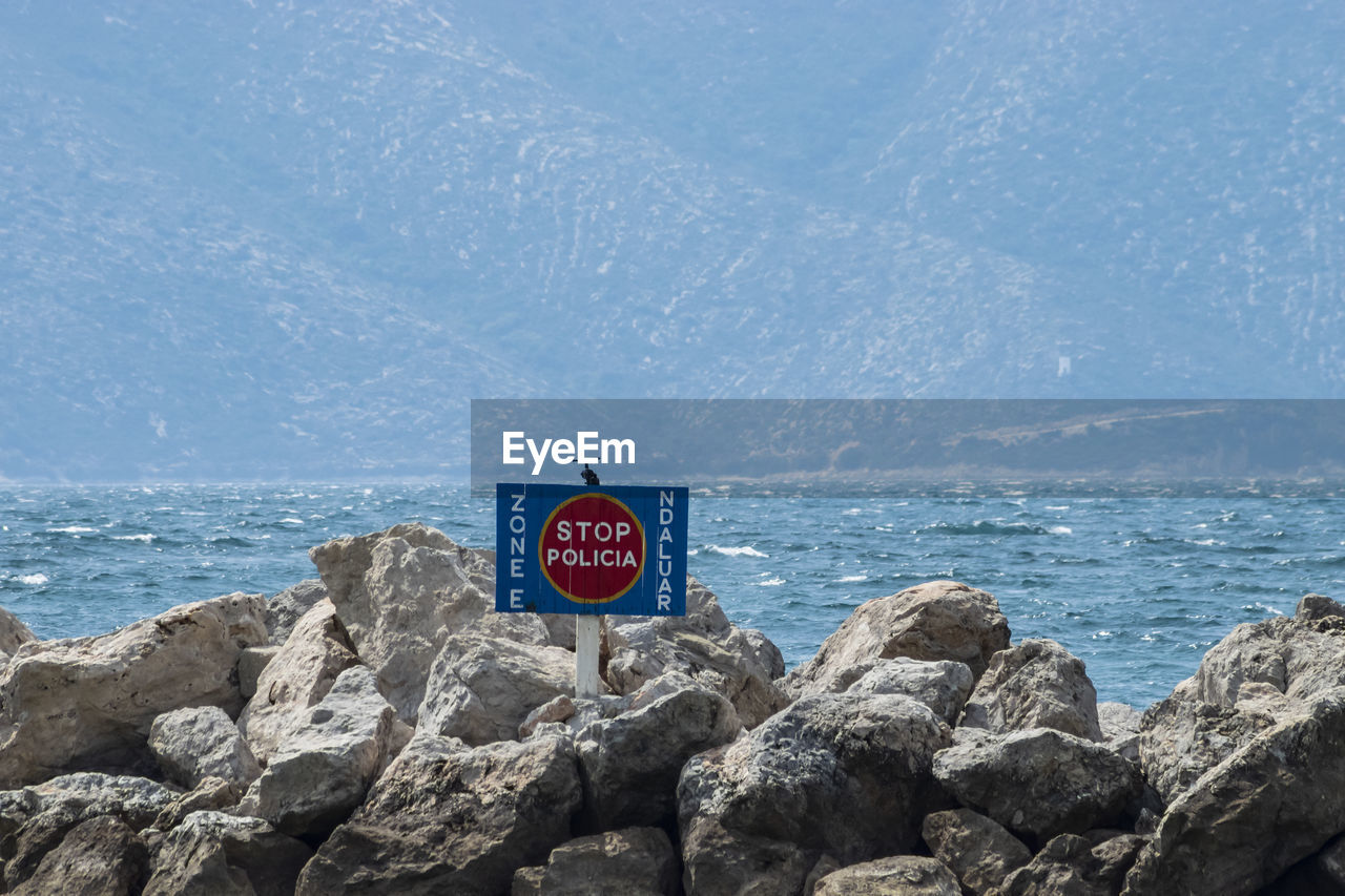 SIGN BOARD ON ROCK AGAINST SEA