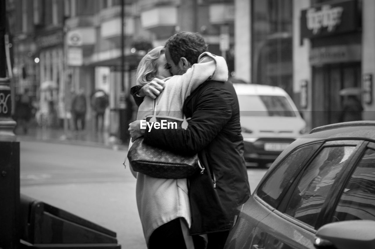 two people, city, street, transportation, mode of transportation, car, motor vehicle, love, adult, togetherness, men, couple - relationship, architecture, real people, city life, three quarter length, women, people, standing, positive emotion, city street
