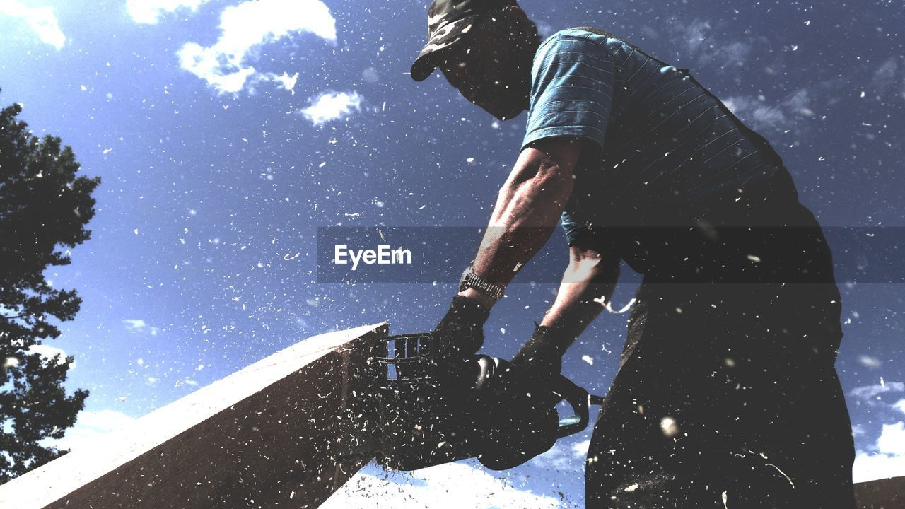 Low Angle View Of Worker Sawing Wooden Plank With Electric Saw