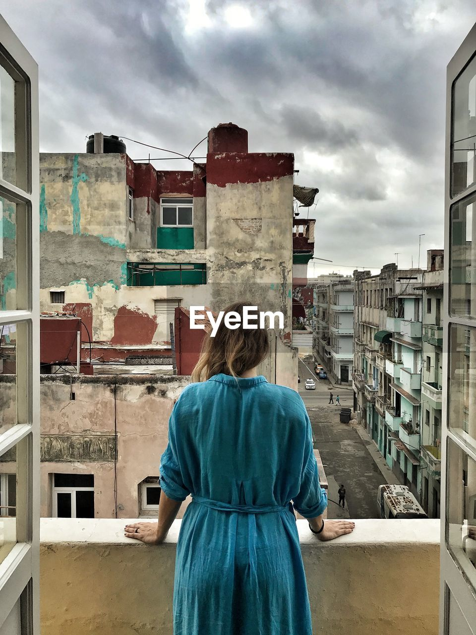 Rear View Of Mid Adult Woman Standing In Balcony Against Cloudy Sky